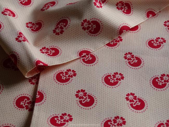 Coupon de coton à fond beige rosé avec motif de fleurs stylisées framboise