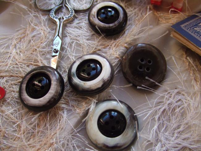 Gros boutons ronds en imitation corne nuance blanc, brun et noir.