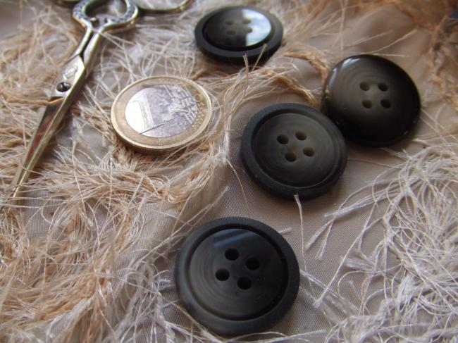 Gros bouton noir et gris, brillant au centre, mat en bordure.